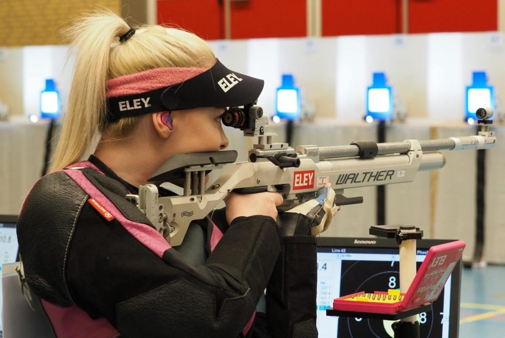 a young woman shooting an air rifle in ISSF Competition